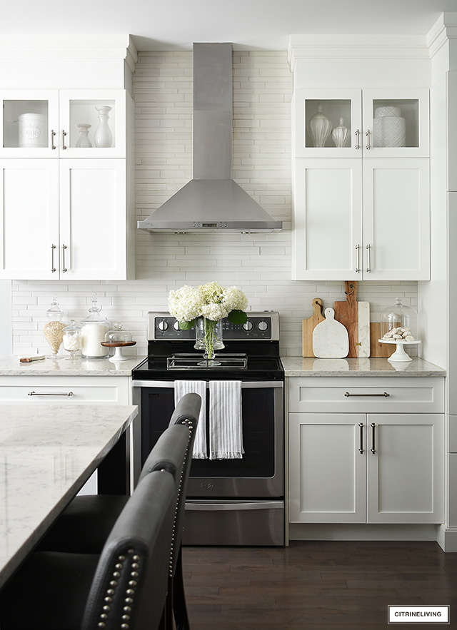 White kitchen cabinets, stainless steel vent hood, brushed silver hardware.