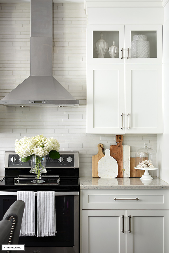 White kitchen cabinets, silver handles, stainless range hood and light grey tile backsplash.