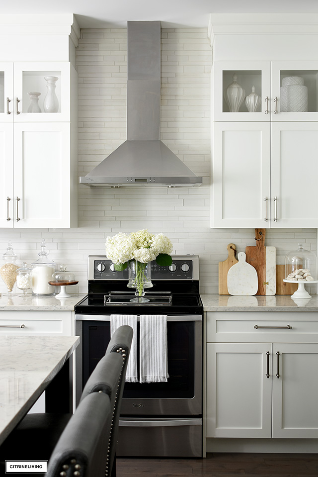 White kitchen cabinets, silver handles, stainless range hood and light grey tile backsplash. A pretty collection of wood and marble cutting boards and glass apothecary jars.