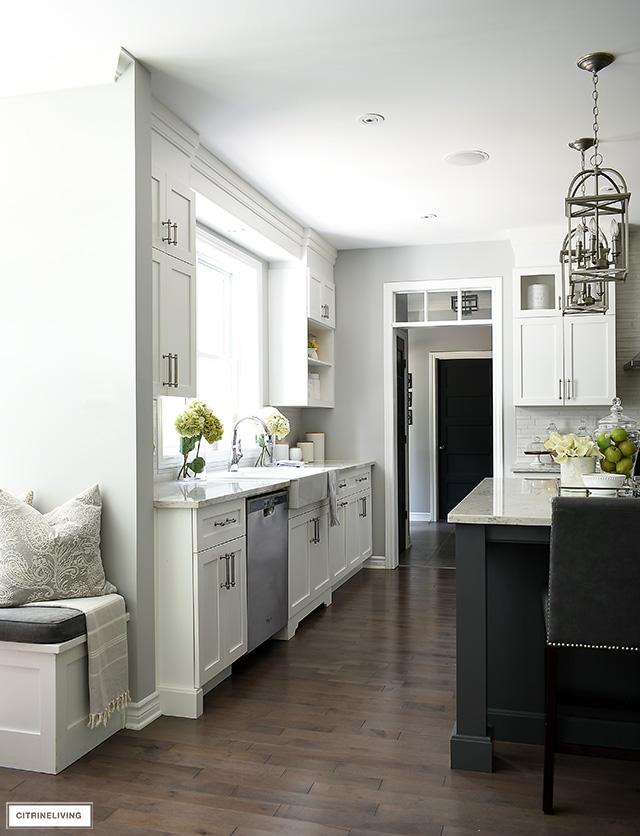 Classic and elegant white kitchen with medium toned hardwood floors.