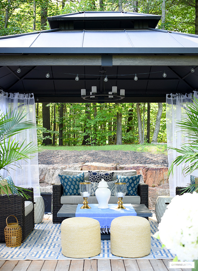Gorgeous gazebo with white drapes, blue and white decor and patio furniture for lounging.