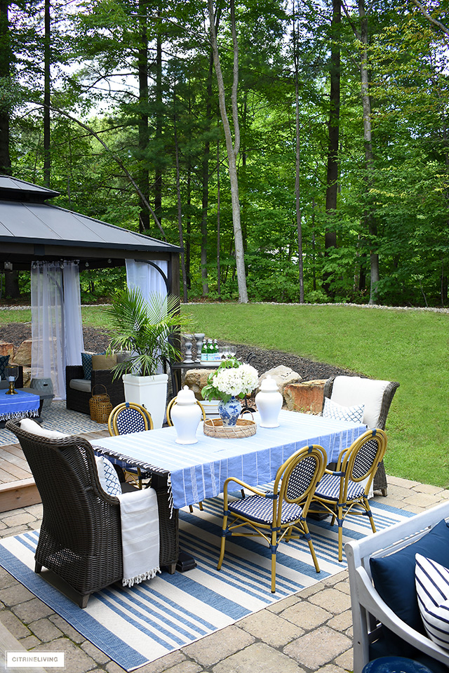 Beautiful backyard patio dining table with wingback chairs, bistro chairs, striped table cloth, ginger jars and hydrangeas.