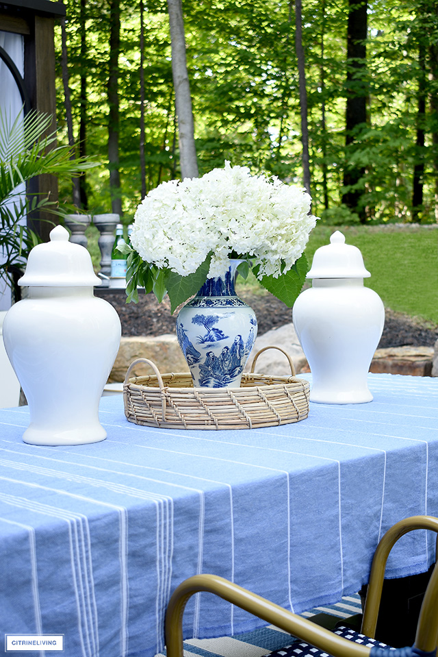 Outdoor dining table centrepiece, blue and white vase with hydrangeas, white ginger jars and rattan tray.