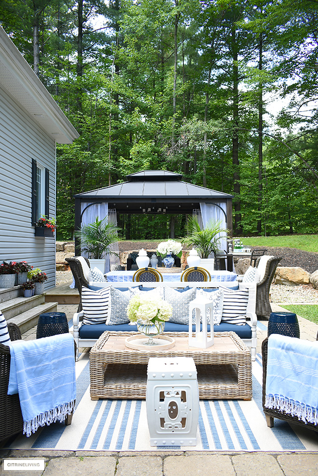 Gorgeous outdoor patio with blue and white decor, pillows, rugs and throws.