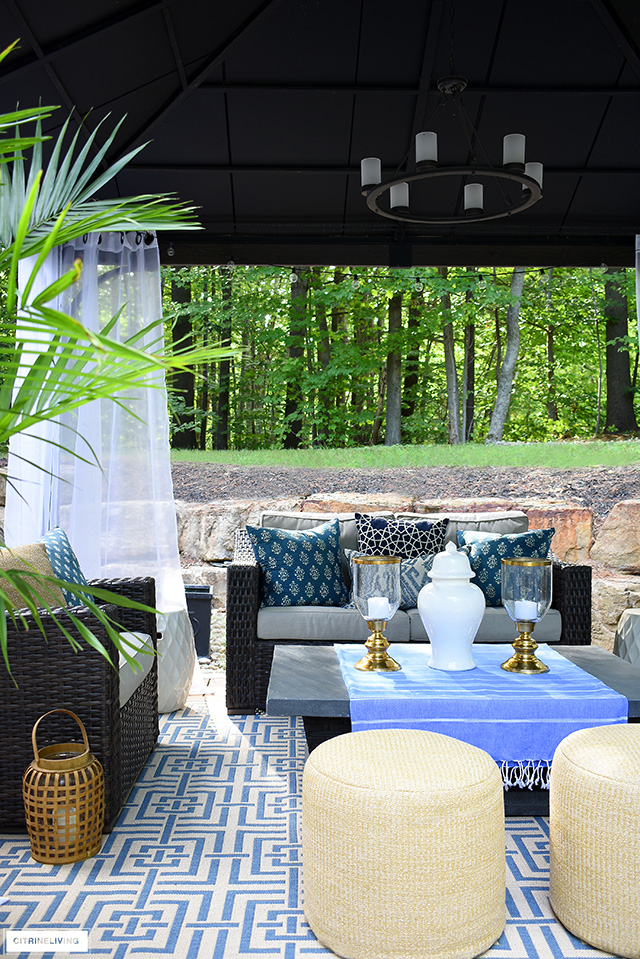 Outdoor gazebo with rattan furniture blue and white pillows and rug, woven poufs and white drapes.