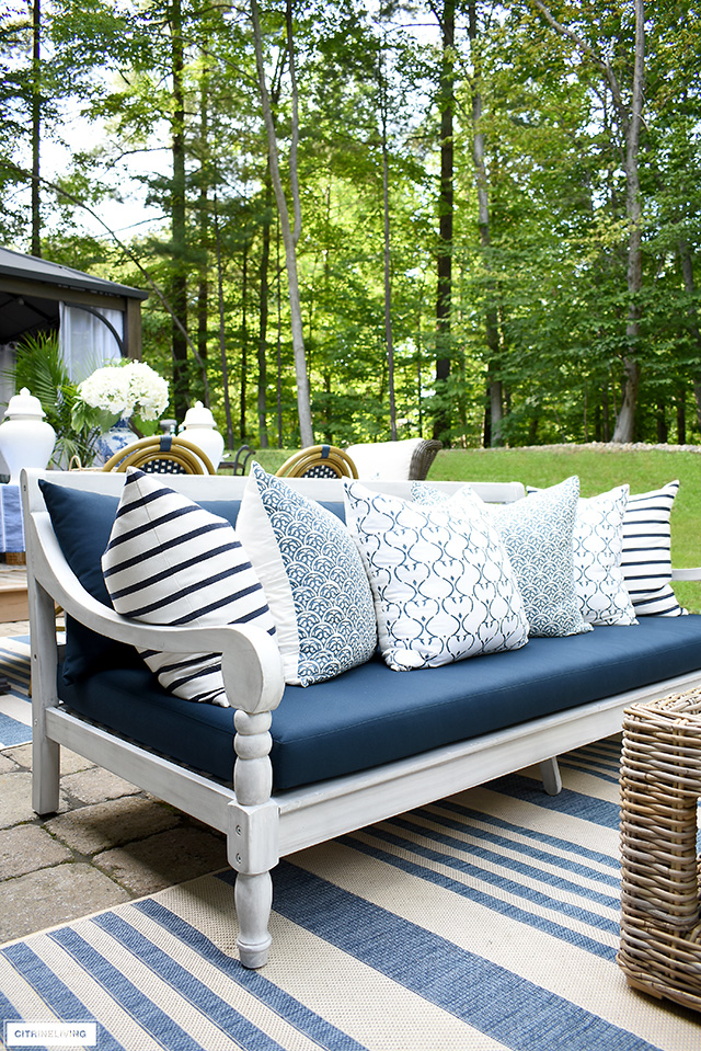 Beautiful outdoor navy and white daybed layered with blue and white block-print pillows.