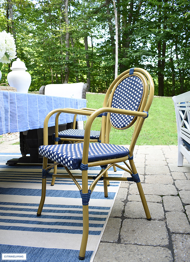 Outdoor dining table with navy and white bistro chairs and beige and blue striped rug.