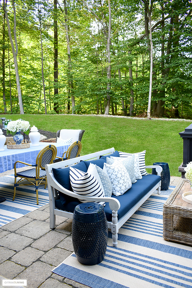 Beautiful outdoor patio with navy and white sofa filled with blue and white block-print pillows.