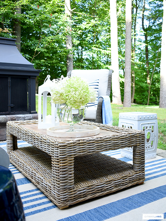 Wicker outdoor coffee table with hydrangeas.