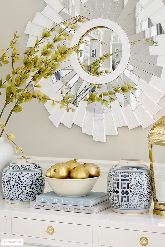 An elegant fall display with blue and white ginger jars, gold faux fruit and faux branches