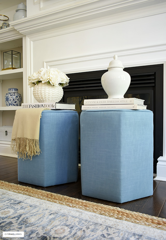 A beautiful pair of blue upholstered hexagonal ottomans topped with books, ginger jars, and a floral arrangement is a gorgeous additions to any space.
