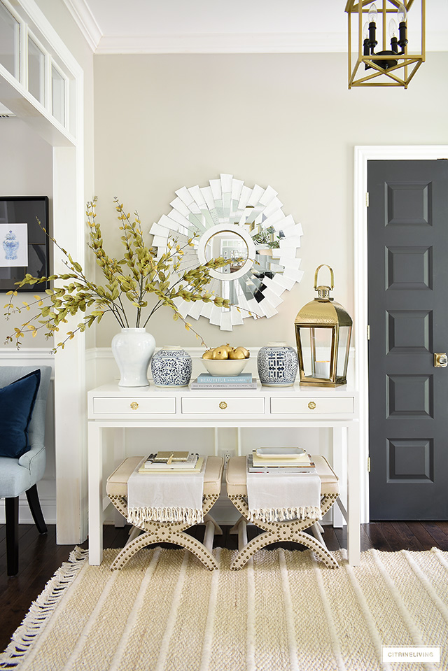 Elegant entryway decorating with a chic console table adorned with blue and white ginger jars, faux gold fruit, a gold lantern and faux branches.