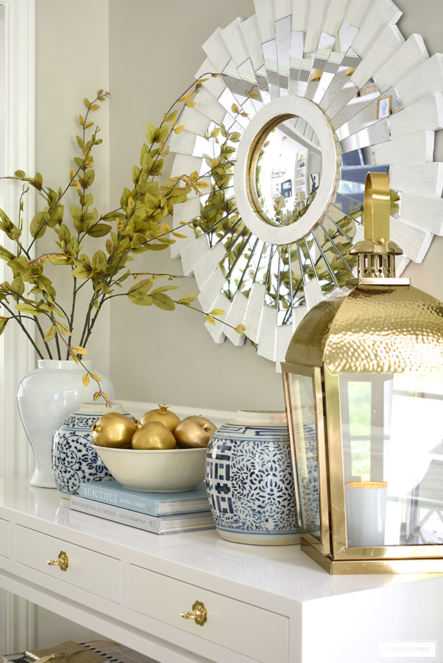An elegant fall decorating vignette with beautiful ginger jars, faux fruit and branches, and gorgeous gold accents.