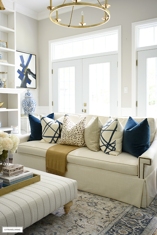 A stunning arrangement of luxe, throw pillows for fall, in navy, brown, cream and soft gold.