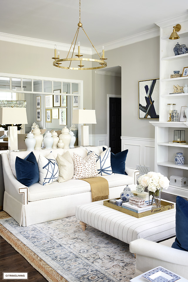 White living room sofa with luxe throw pillows in navy, brown, cream and a gold shimmer. Beautiful and luxe for the fall season.