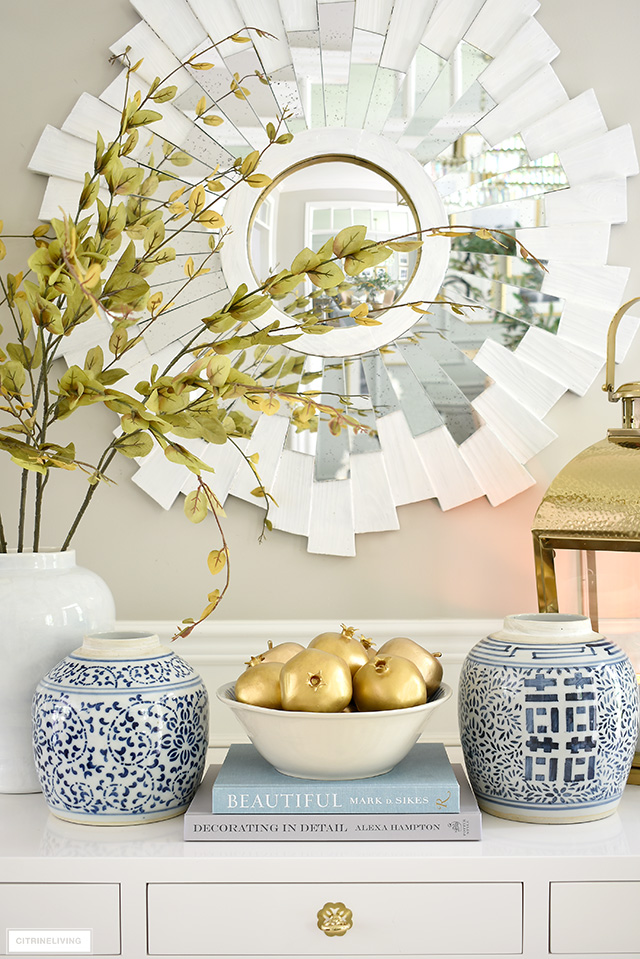 Gold painted fruit, faux branches, ginger jar and a gold lantern are perfect for a beautiful fall display.