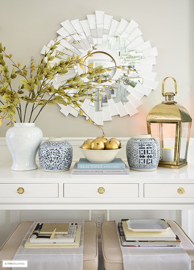 A layered console table for fall with blue and white ginger jars, gold painted fruit, faux branches, and gold lantern.