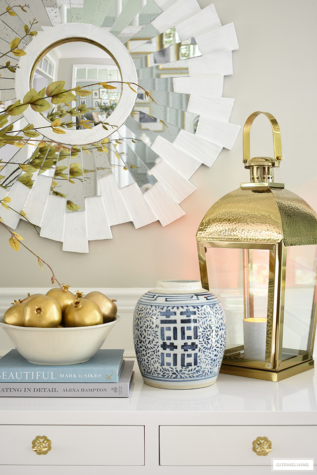 A gorgeous fall display with gold faux fruit, blue and white ginger jar and oversized gold lantern.