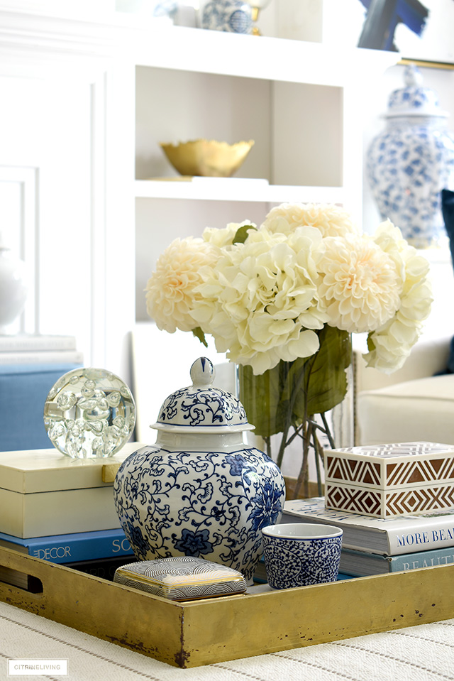 Blue and white chinoiserie, decorative boxes, pretty objects and faux florals on a gold tray make a chic statement.