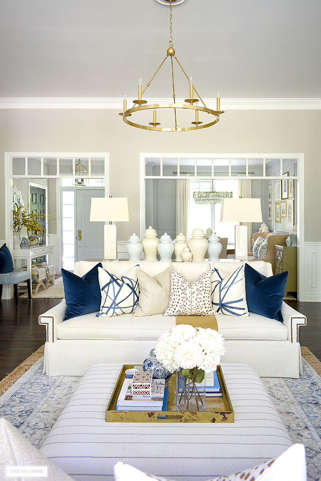 Living room decorated for fall with beautiful pillows, ginger jars, navy brown, cream and gold accents.