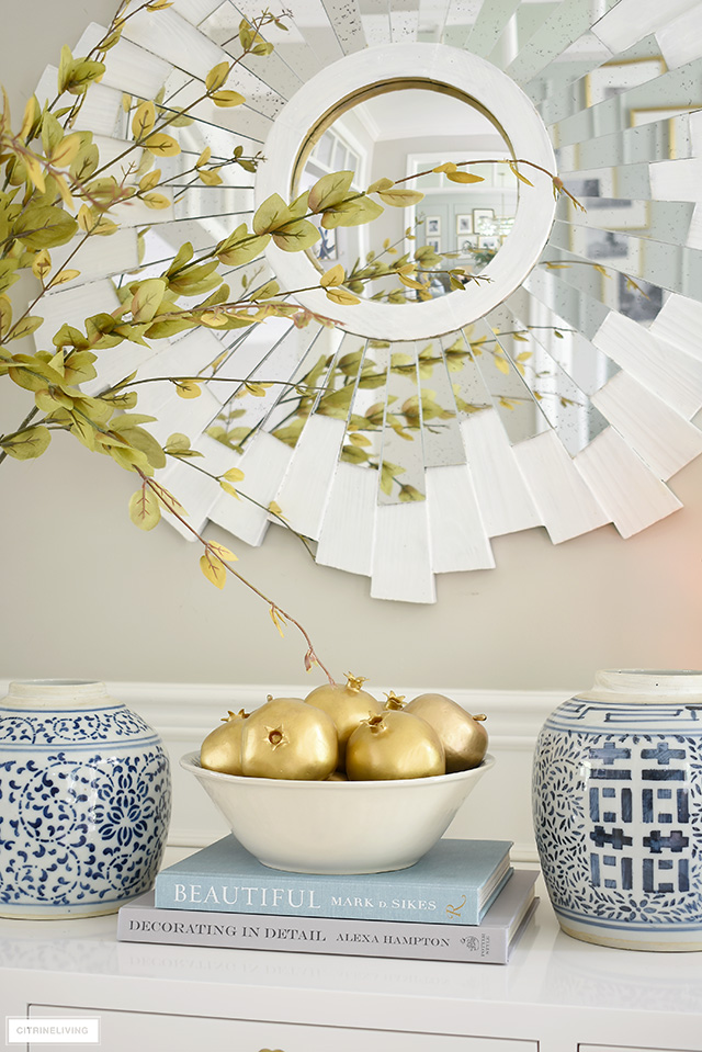 An elegant display for fall using blue and white ginger jars, faux gold painted fruit and faux branches.