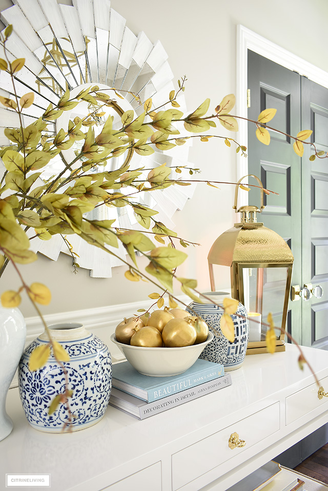 Fall decorating with ginger jars, faux fruit painted gold, a gold lantern and faux branches.