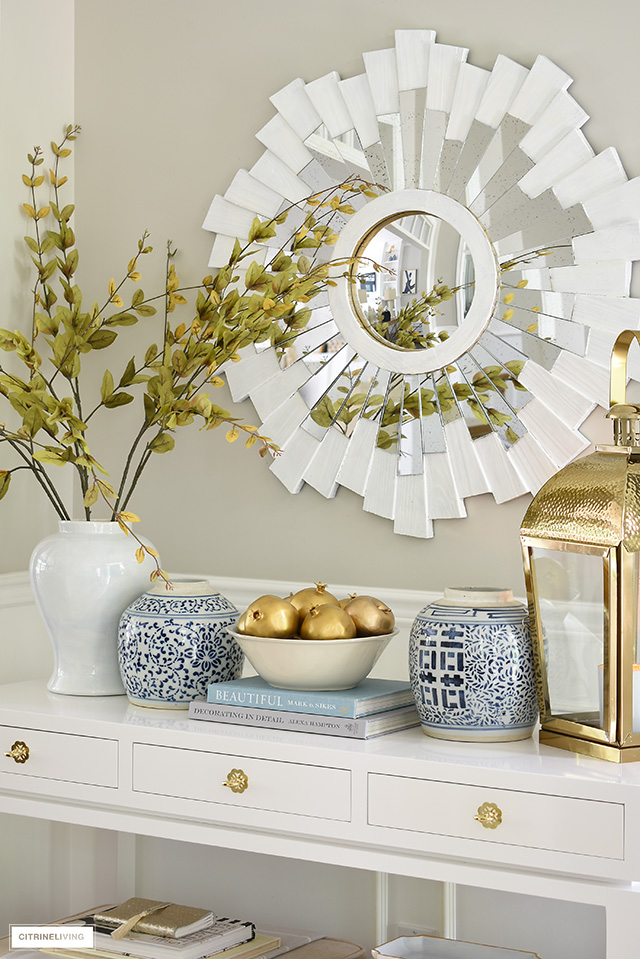A beautiful fall console table, elegantly decorated with ginger jars, gold accents and faux branches and fruit.