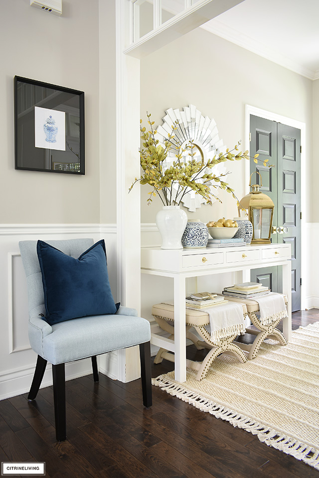 An elegant entryway decorated for fall with touches of navy, gold, beiges, soft blue and white.