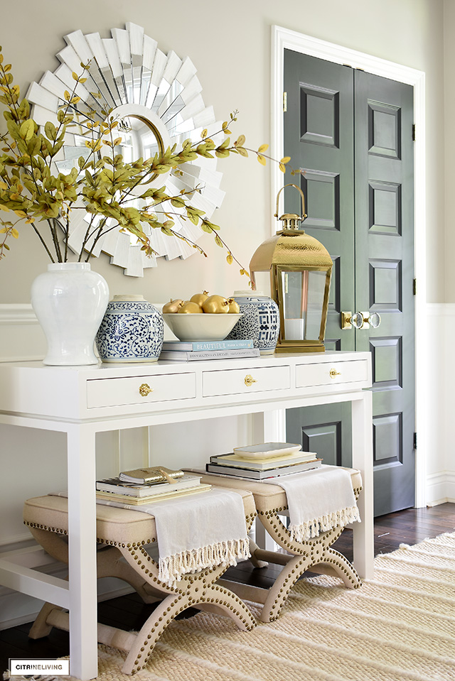 A beautiful and elegant entryway console table layered with ginger jars, gold lantern, gold fruit and faux branches.