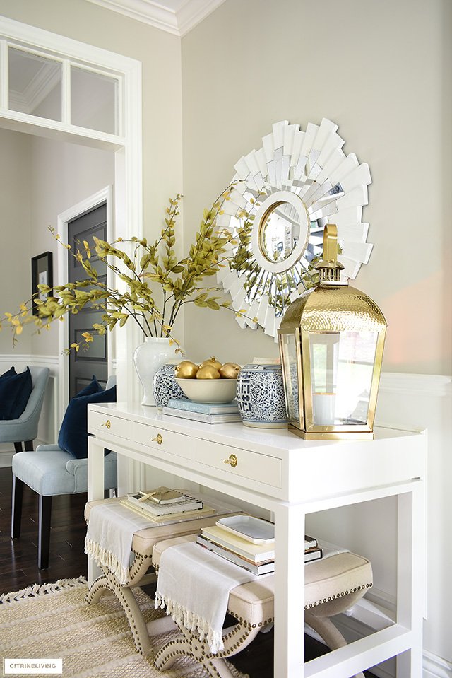 Foyer console table decorating for fall - gold, blue and white, faux branches and fruit are a gorgeous welcome for the season!