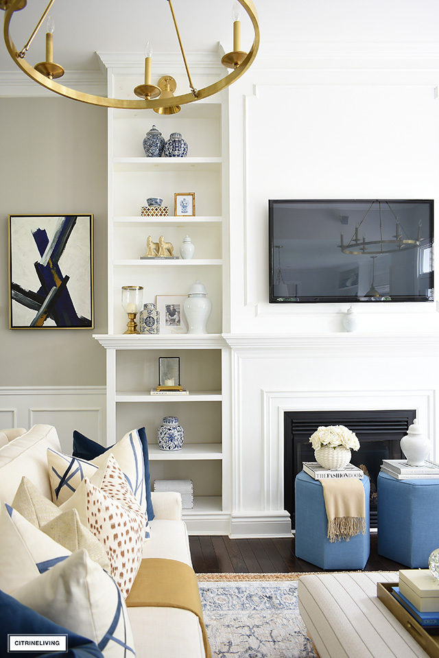 Simple and elegant shelf styling with blue and white ginger jars, gold accents, and pretty objects.