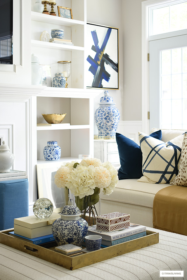 Living room decor for fall featuring beautiful blue and white accents, faux florals, throw pillows in rich colors.