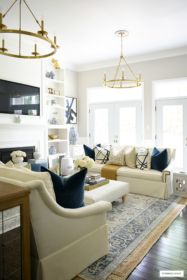 A gorgeous fall decorated living room space with beautiful white sofas, vintage rug, navy, brown, cream and gold accents.