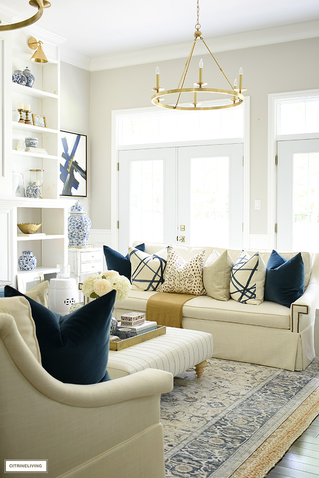 Living room decor with navy blue, gold, cream, camel and brown is chic and elegant for fall.