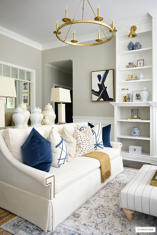 Elegant and tailored whit sofa with a mix of beautiful throw pillows for fall in luxe navy velvet, brown and cream spotted Les Touches fabric, and Kelly Wearstler channels in navy.