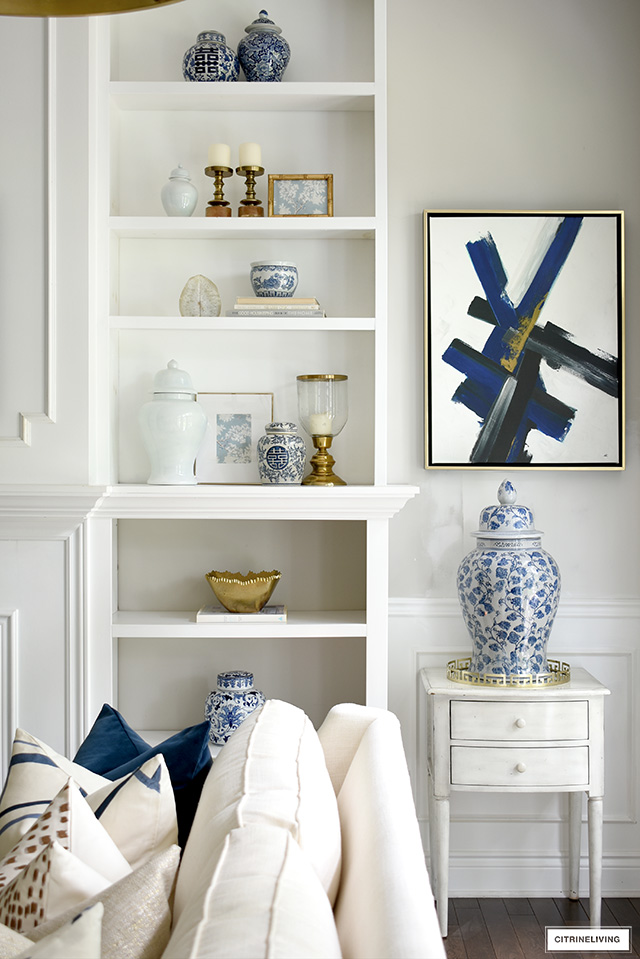 Bookshelff styling ideas with blue and white ginger jars, solid ginger jars, brass hurricane lanterns, and beautiful objects to create interest and tell a story. Modern art accents the color scheme.