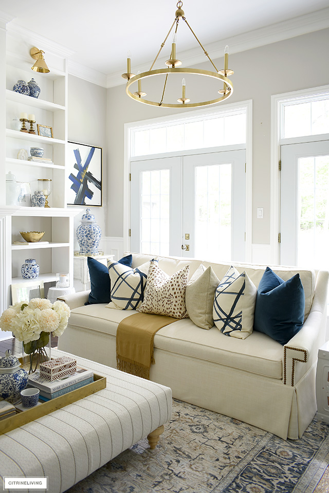 White sofa adorned with luxe throw pillows for fall, in rich navy, brown, cream and gold.