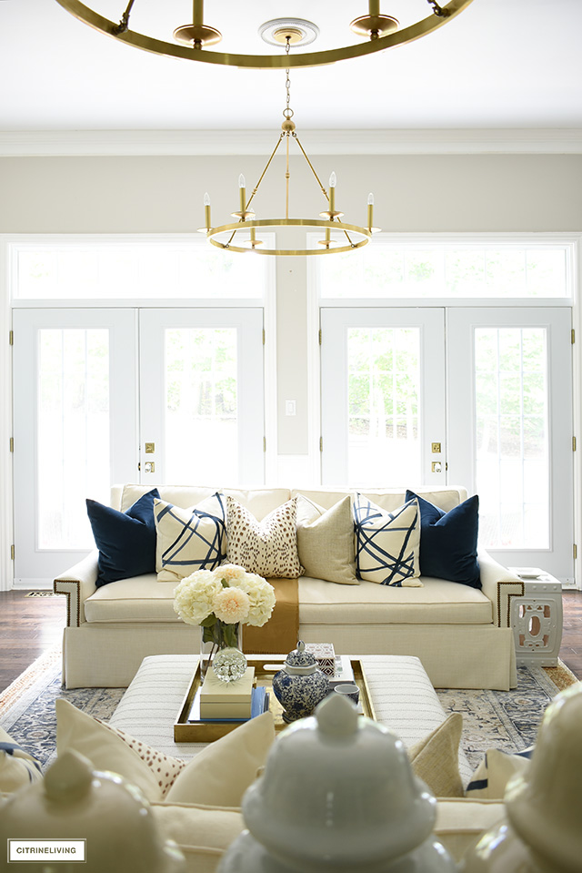 A beautiful living room with natural light features a chic fall decorated space with rich, warm colors.