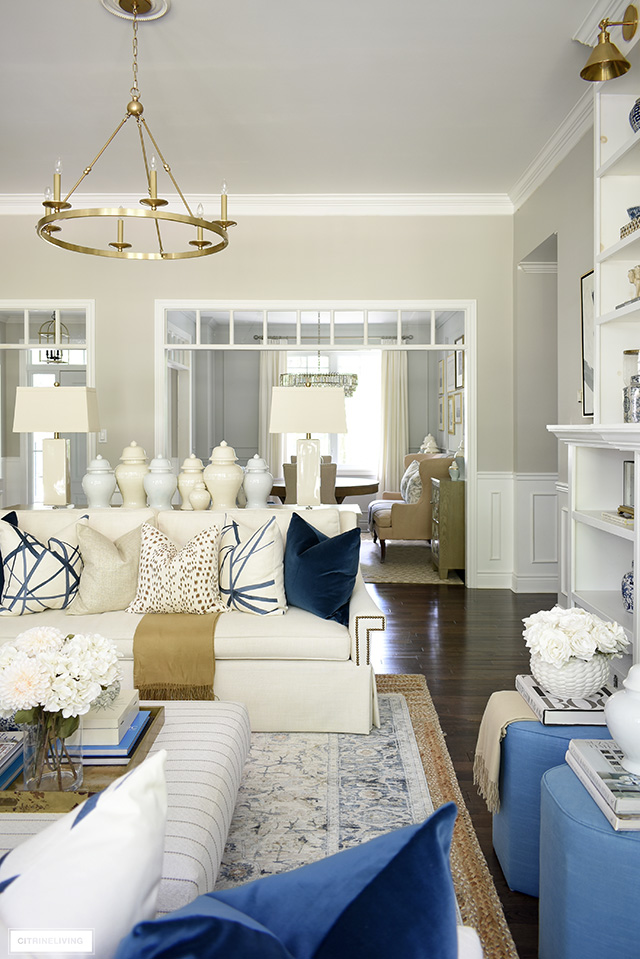 Fall living room decorating ideas with rich, luxe colors, beautiful throw pillows, a vintage rug ad ginger jars.