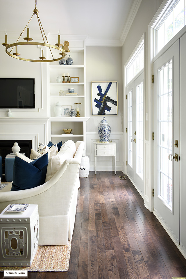 An open living room decorated for fall, french doors with transoms allow gorgeous natural light. Blue and white chinoiserie mixed with gold accents is sophisticated and elegant.