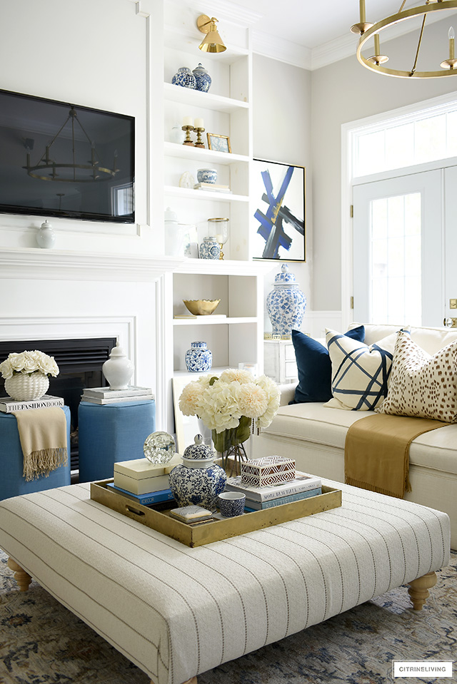 Living room ottoman styling with a gold tray, pretty boxes, design books and faux flowers.