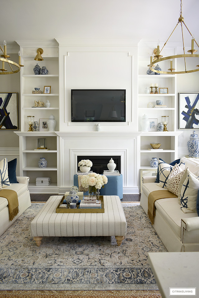 Living room decorated for fall - builtin bookshelves with blue and white chinoiserie accents paired with gold and wood accents for a luxe layered look.