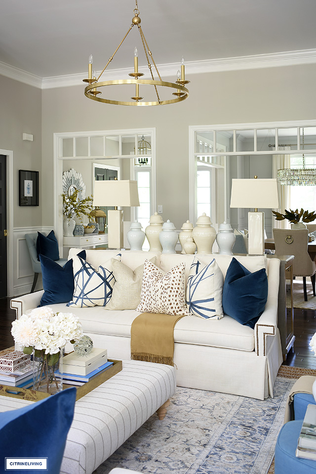 Living room decorated for fall with beautiful navy blue, brown and cream pillows, ginger jars, and a vintage rug.