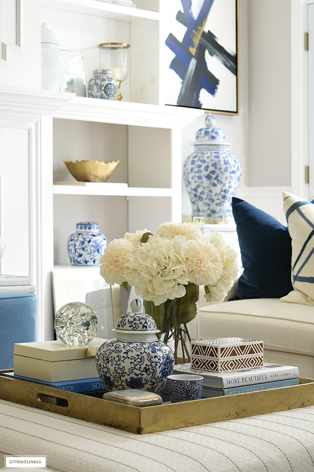 A beautiful coffee table or ottoman vignette with faux flowers, ginger jars, decorative boxes and design books.