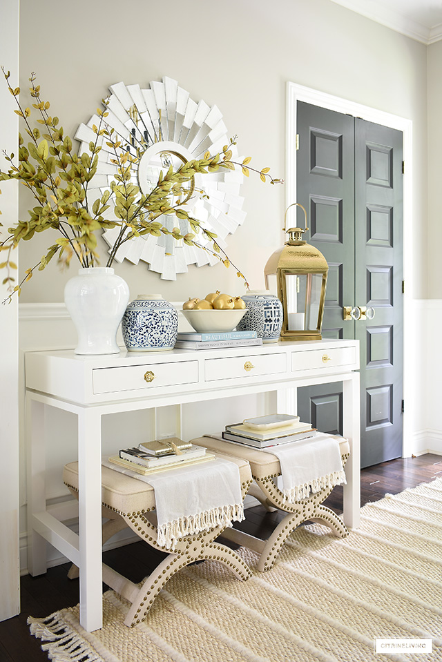 A fresh and elegant take on fall decor with soft colors, gold accents, faux branches and gold painted faux fruit.