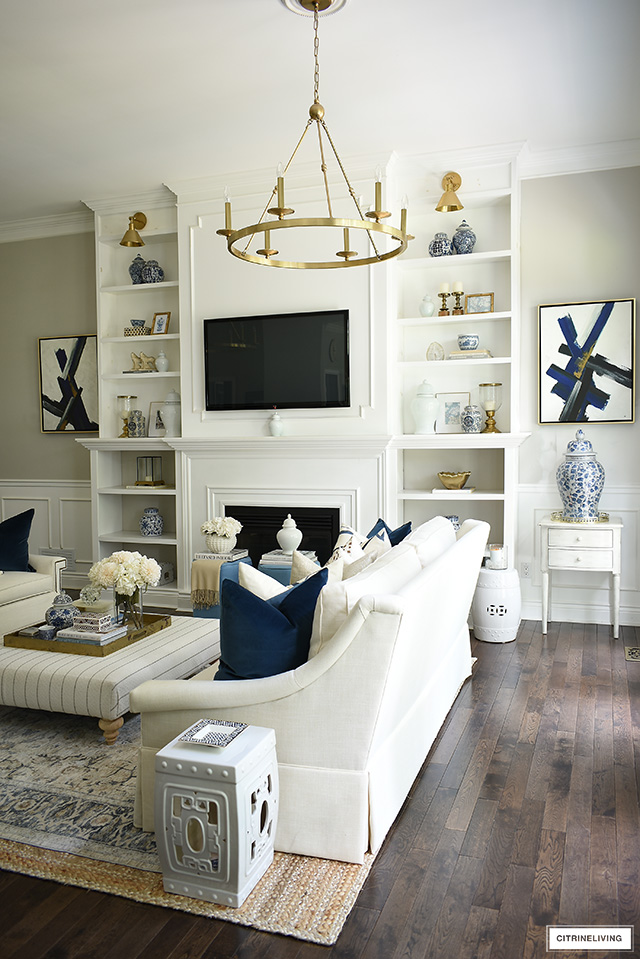 Chic and luxe fall living room decor with floor to ceiling builtin bookshelves, white sofas, layered rugs and blue, white and gold accents.