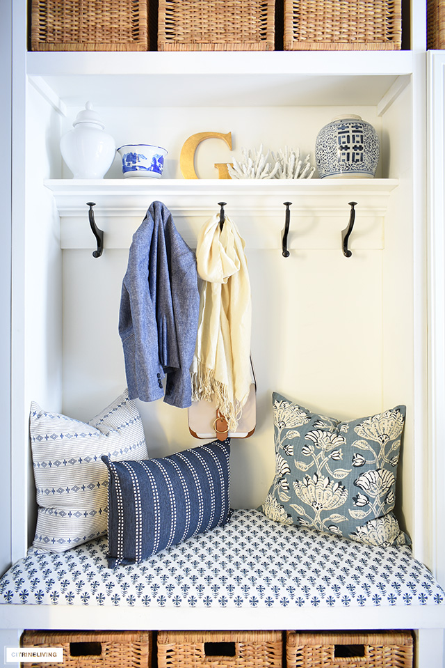 Beautiful blue and white pillows and bench fabric are a gorgeous addition to this coastal look mudroom + laundry room builtin bench area.