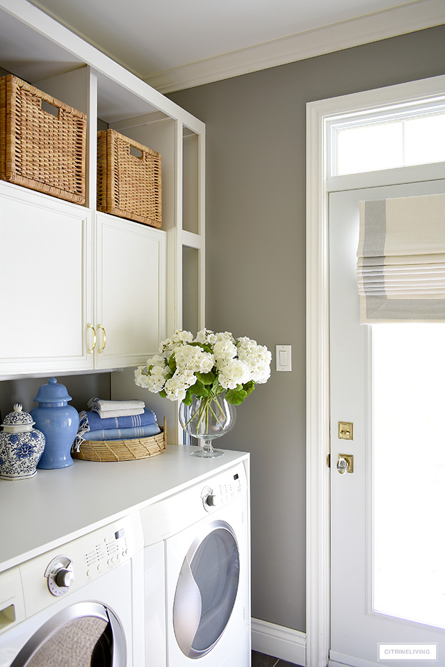 Style your laundry room with pretty details! Beautiful woven baskets and trays, turkish bath towels, faux flowers and ginger jars are a chic touch.