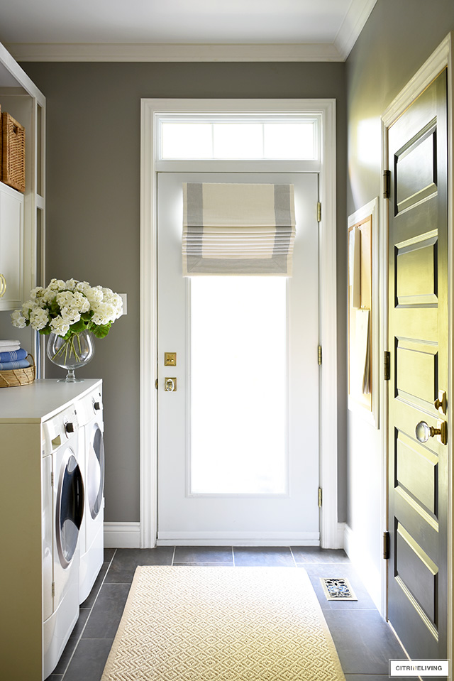 Beautiful mudroom and laundry room with exterior french door, accented with a tailored roman shade.