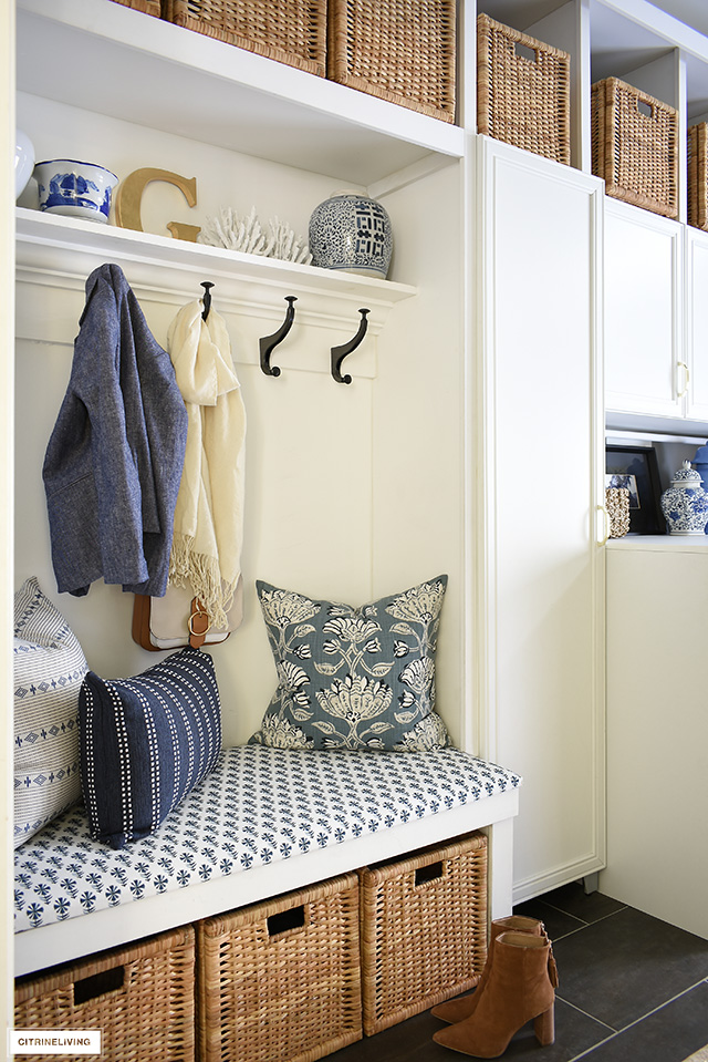 Laundry room upholstered bench with gorgeous blue and white fabric and pillows. Ginger jars are the perfect accessory!